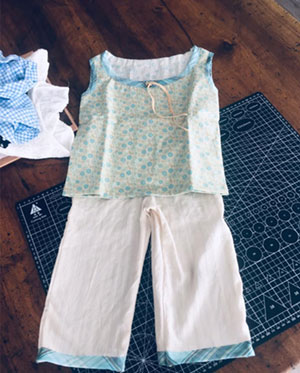 Petit ensemble, composé d'un haut sans manche et d'un pantalon bleu et blanc pour petite fille