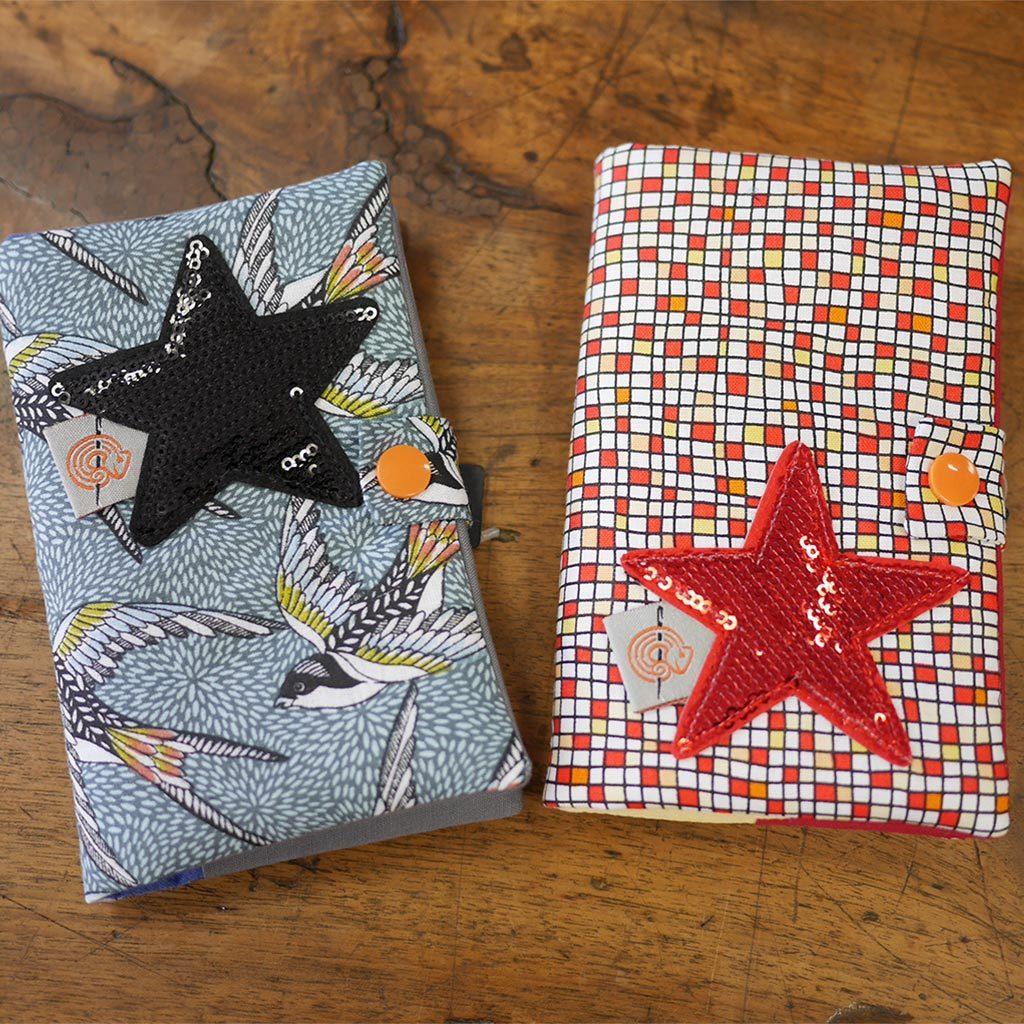 Petit carnet petit carreaux fournit recouvert en tissus agrementée d'une étoile en simili-cuir de couleur noire ou rouge et d'une pression