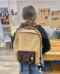 Réalisation d'un sac à dos marron avec petite poche sur le devant porté par Olivia