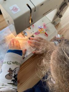 Atelier Enfants : fillette en train de coudre avec la machine BERNINA, une fermeture éclaire pour sa trousse