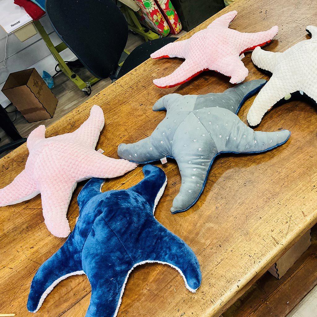 Cinqs Doudou étoiles de mer de couleur : deux roses, une bleue, une grise et une blanche