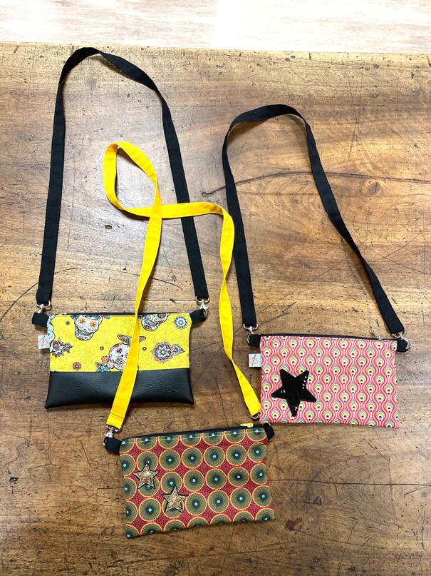 Présentation de trois pochettes en bandoulière, noir et jaune, noir et rouge avec une étoile noire et la troisième avec une couleur dominante prune aux motifs ronds
