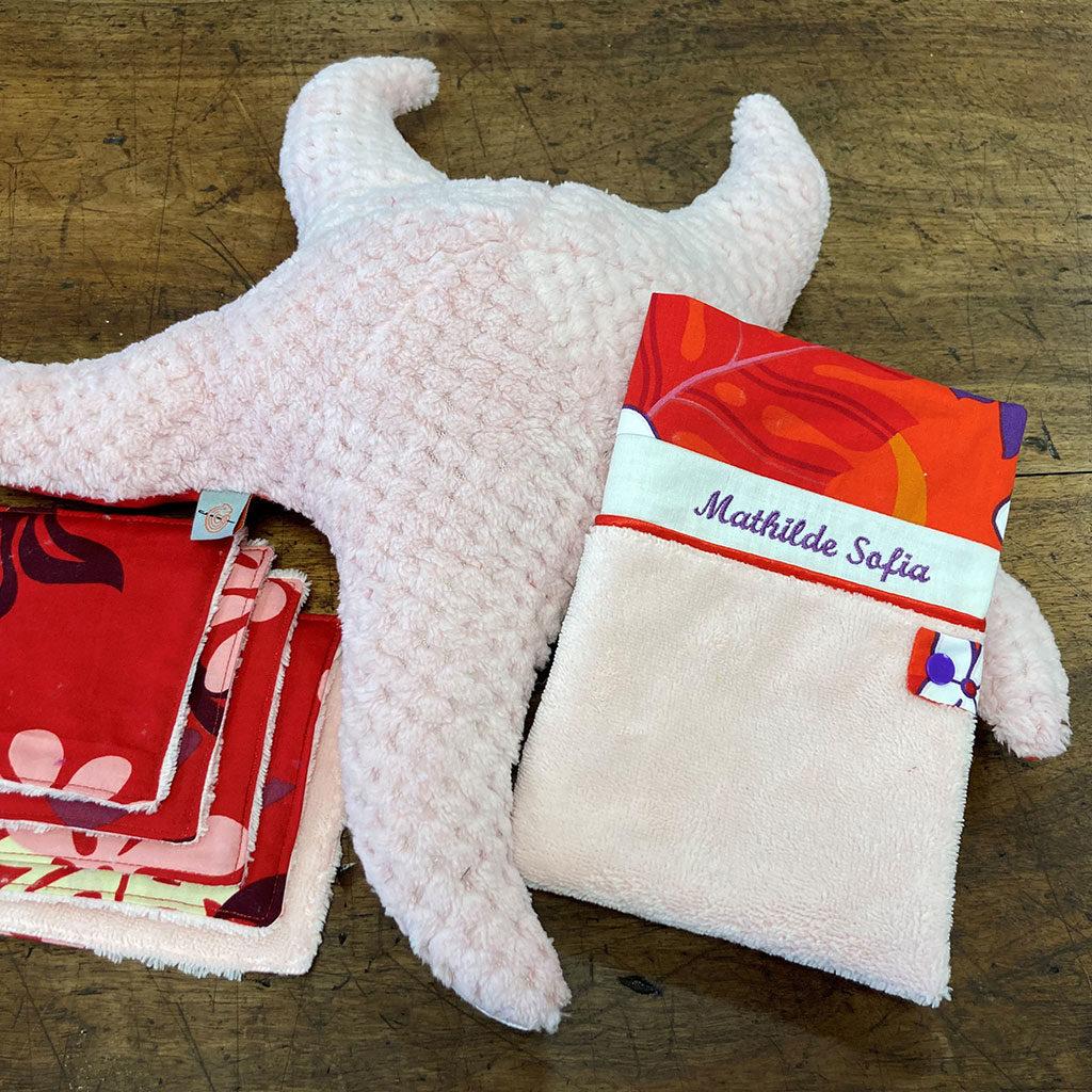 Présentation du carnet de santé avec son protège carnet réalisé en tissus accompagné d'une étoile de mer et des lingettes de couleurs rose et rouge