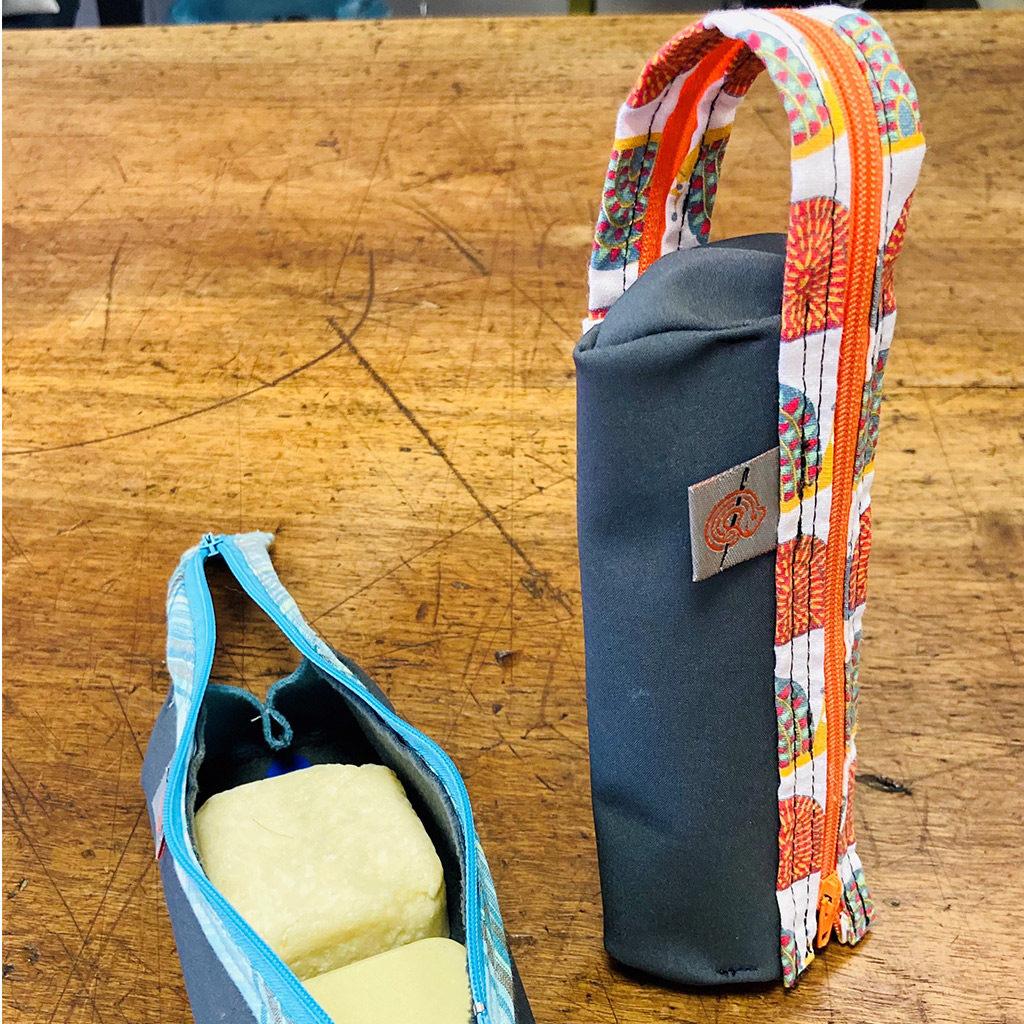 Deux trousses pour deux savons de couleur grise avec une fermeture éclair orange pour l'une et bleu pour la deuxième