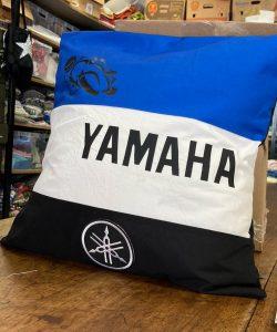 Coussin YAMAHA réalisé par Laura. Couleurs : bleu, blanc et noir avec le logo de Yamaha en blanc et un pictogramme d'une moto en noir