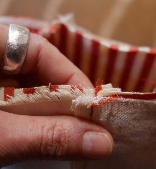 Main de Camille réalisant la couture d'un petit pot à linguette
